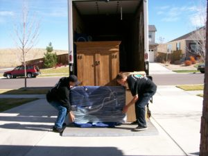 Movers and Packers putting a wardrobe on a moving truck.